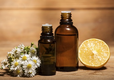 Lemon and chamomile essential oil on wooden background